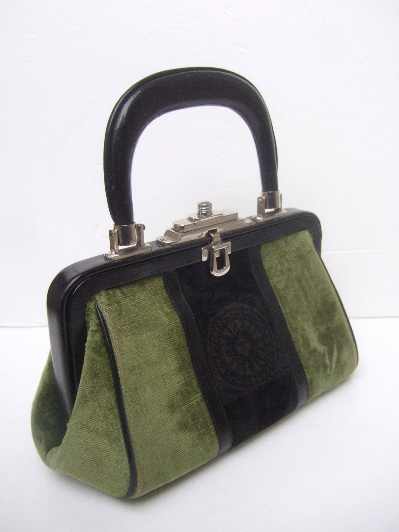 Roberta Di Camerino Chic moss green & ebony velvet handbag c 1970s   The iconic Italian handbag is covered with plush moss green & ebony velvet  The stylish handbag is designed with a black leather handle & clasp frame Accented with black leather