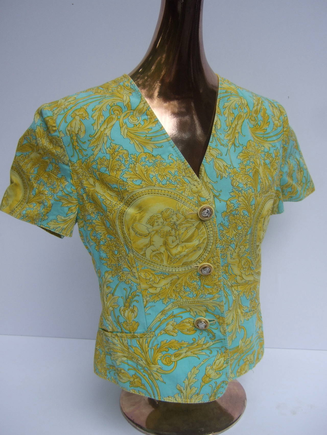 Versace vibrant print Medusa button cotton jacket US Size 10   The bold print is illustrated with cherubs & eagles concealed in the sinuous foliage. The crisp short sleeve cotton jacket is adorned with three ornate silver & gilt metal Medusa