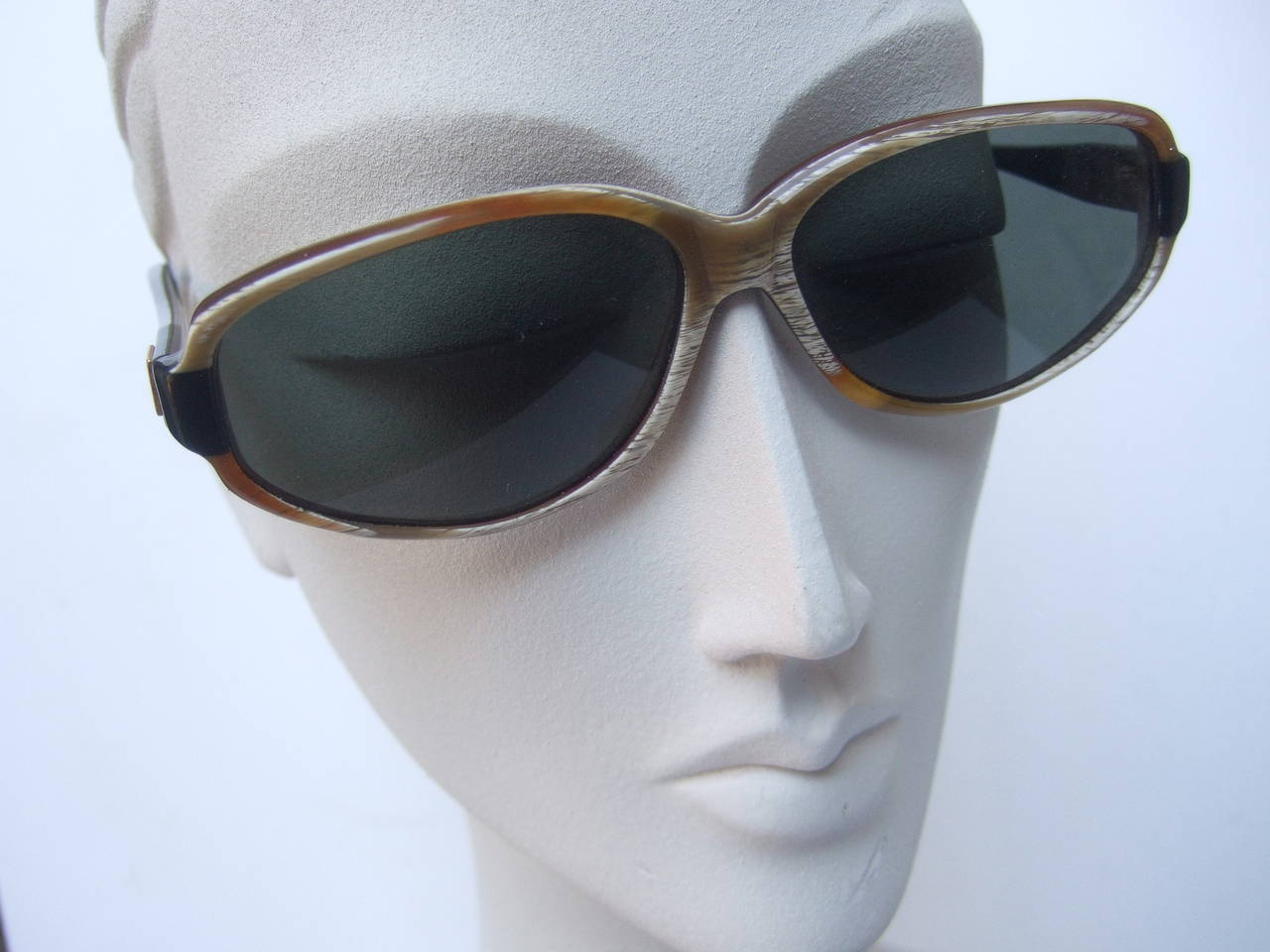 Jean Patou Paris Stylish sunglasses Made in France c 1990 The chic sunglasses are designed with amber lucite horn style frames with white streaks & gray tinted plastic lenses  The sides are designed with ebony lucite with gilt metal  plaques