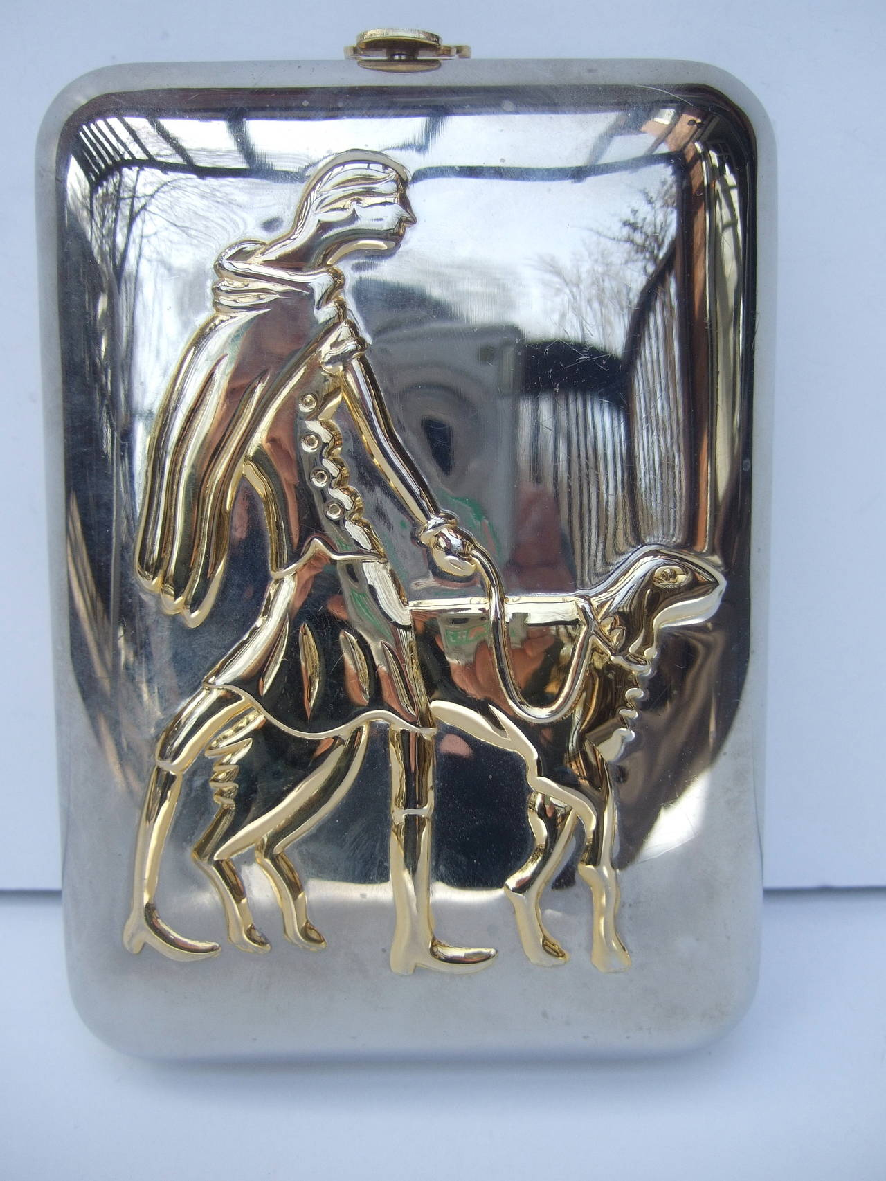Unique figural metal woman evening bag c 1980s The art deco inspired metal evening bag is designed with a gilt metal woman walking her canine companion. The gold metal raised figures  are contrasted with a smooth shiny silver metal