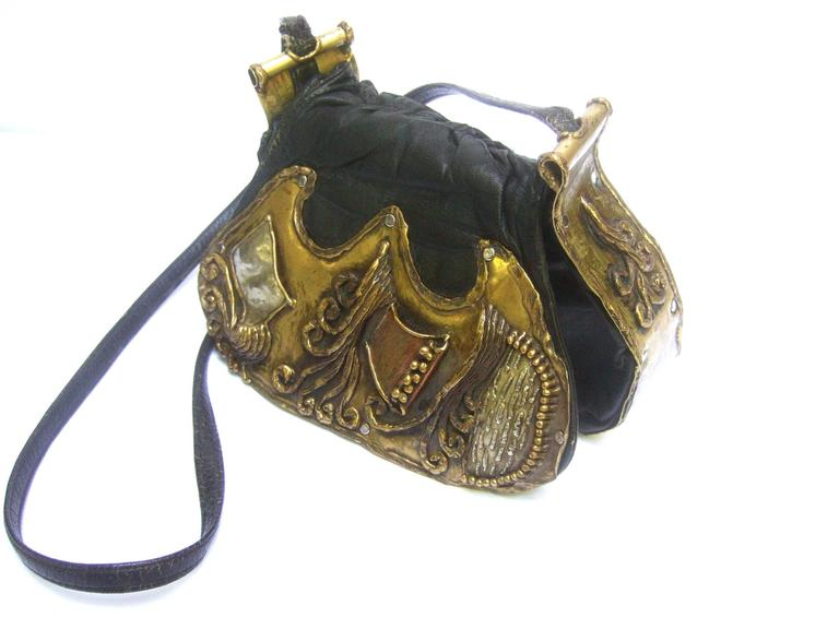 Avant garde brutalist mixed metal artisan handbag ca 1970s The unique handmade shoulder bag is adorned  with sinuous three dimensional mixed metal work designs on the black leather flap cover   The mixed metal work designs are primarily brass