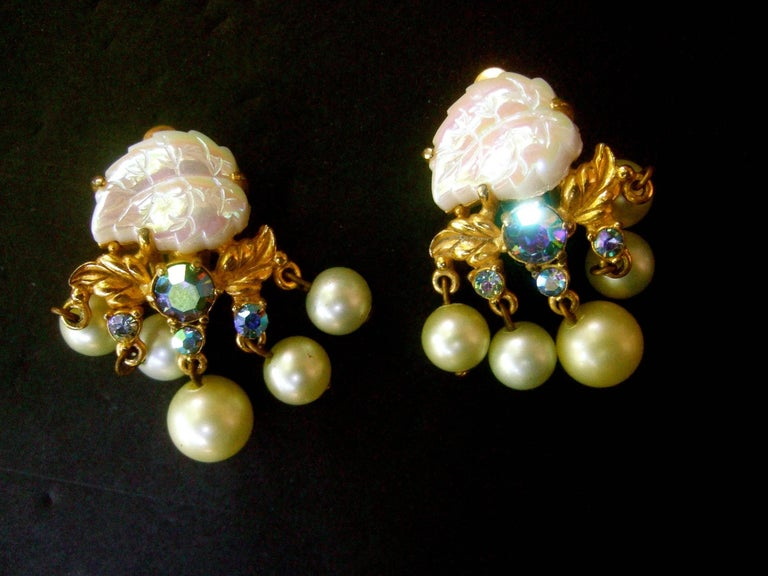 Schiaparelli Dangling pearl aurora borealis earrings c 1950s The midcentury clip on earrings are designed with an  iridescent carved milk glass leaf  Embellished with a cluster of dangling resin enamel pearls. Accented with glittering aurora
