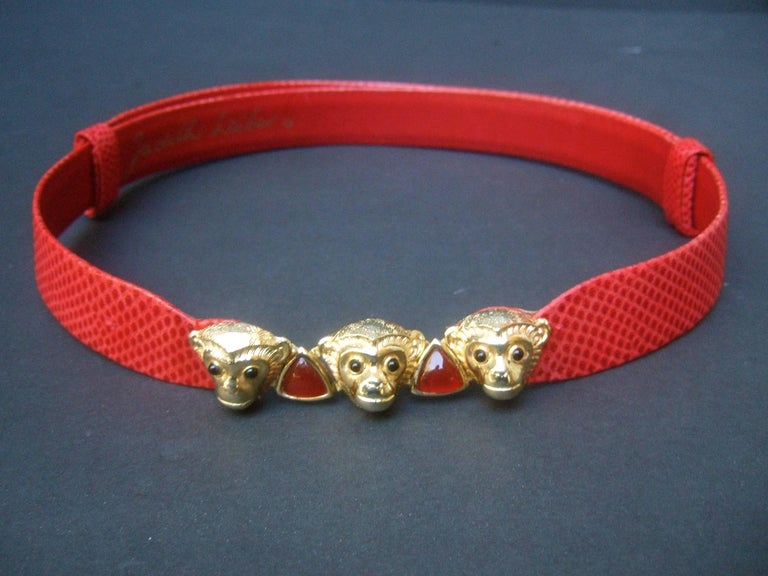 Judith Leiber Charming monkey buckle embossed red leather belt  The stylish belt is designed with a trio of jeweled gilt metal monkeys that serve as the buckle  The adorable monkeys are embellished with tiny black  glass cabochon eyes. The center