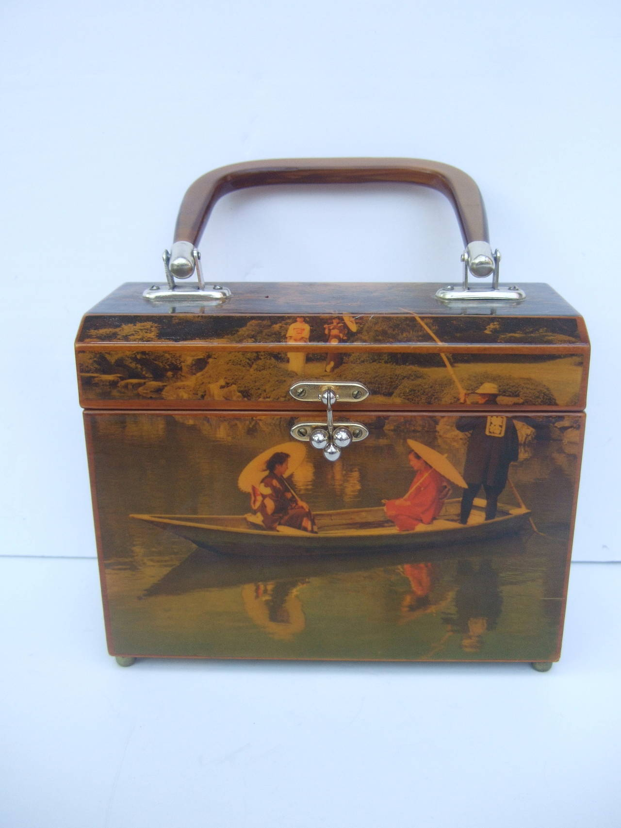 1970s Japanese inspired decoupage Geisha women handbag The unique wood box shaped handbag is illustrated with a pair  of Geisha women floating in a boat. Their reflections are captured in the rippling water   The lid cover is illustrated with