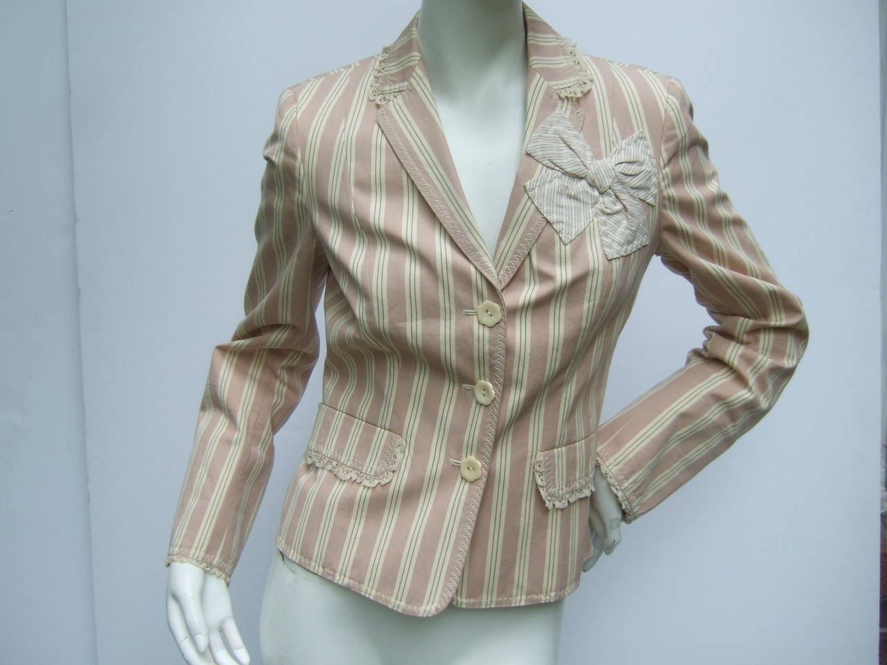 Moschino Cheap & Chic Awning striped cotton jacket US Size 8 The crisp summer jacket is designed with dusty pale pink  stripes combined with tan stripes. One of the chest pockets  is designed with an applique striped bow. The lapel & edges are