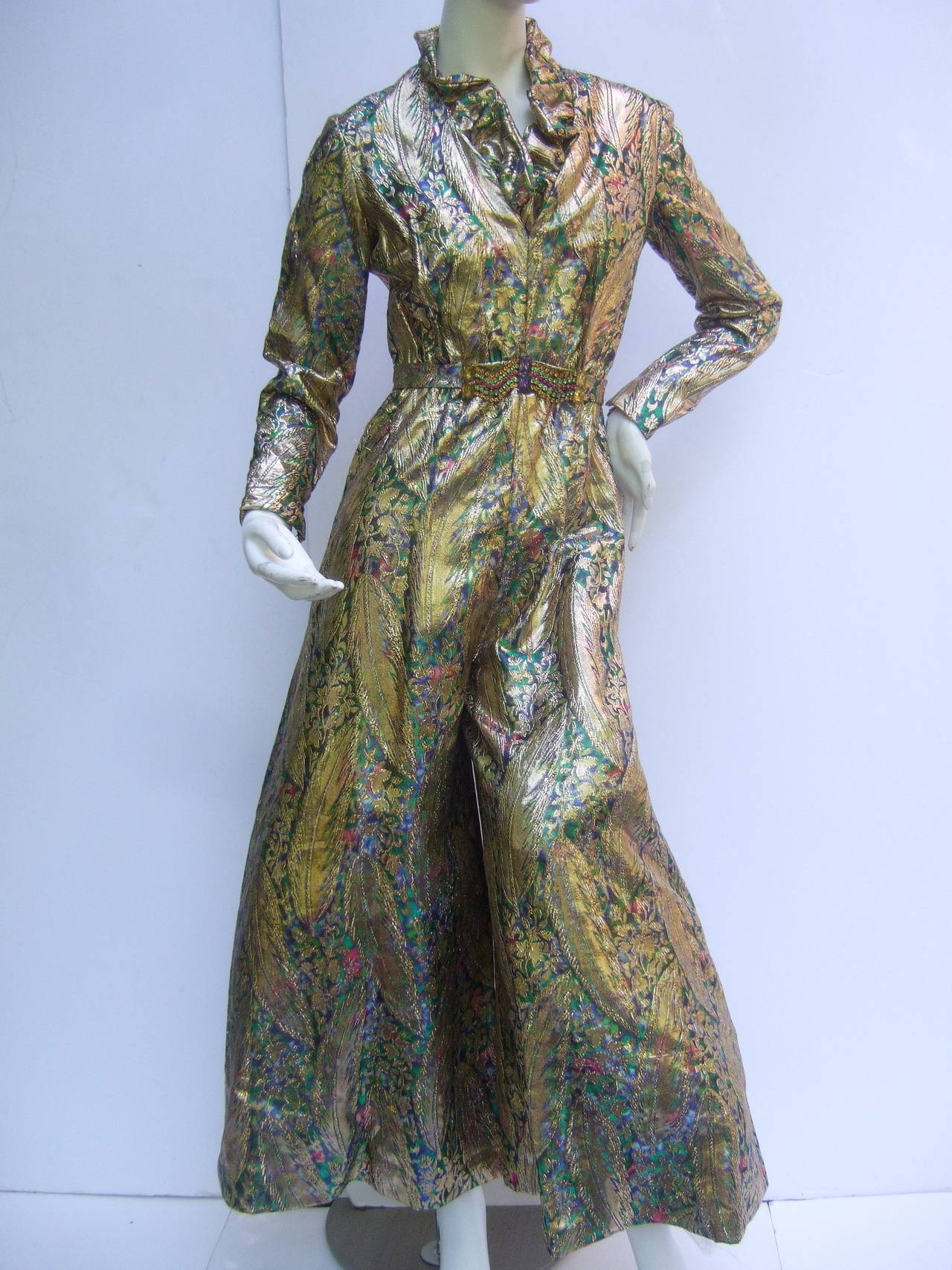 1970s Gold lame peacock feather jeweled jumpsuit c 1970 The exotic lame jumpsuit is designed with gold metallic  feathers with accents of green, blue & fuchsia colors  The lavish gold metallic jumpsuit is embellished with a glittering crystal