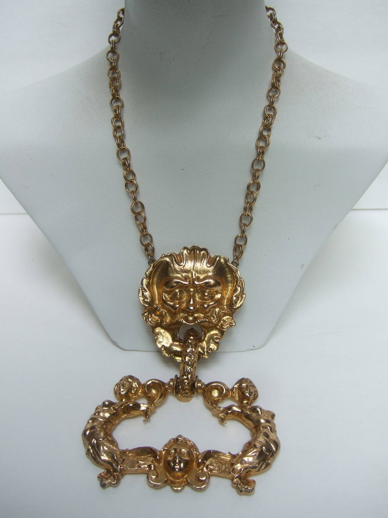 Massive gilt metal figural pendant necklace c 1970 The avant-garde doorknocker pendant necklace is designed with an ornate mythical figural man. Hinged to the figural head is a huge repousse pendant with a pair of siren figures with a woman's face