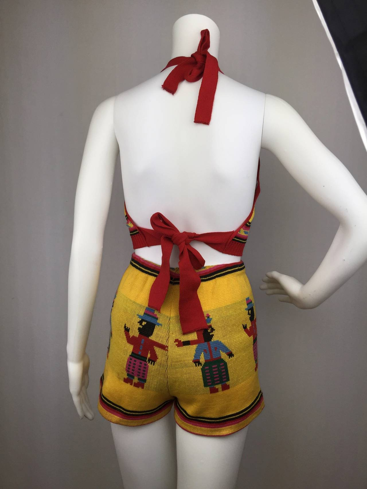 Wonderful two piece by America's original Pop-Art fashion designer, Betsey Johnson.    Graphic knit depicting an Aztec couple.  A halter tie top and high-waisted, elasticated, short-shorts.  Looks so cool on! Fits over several