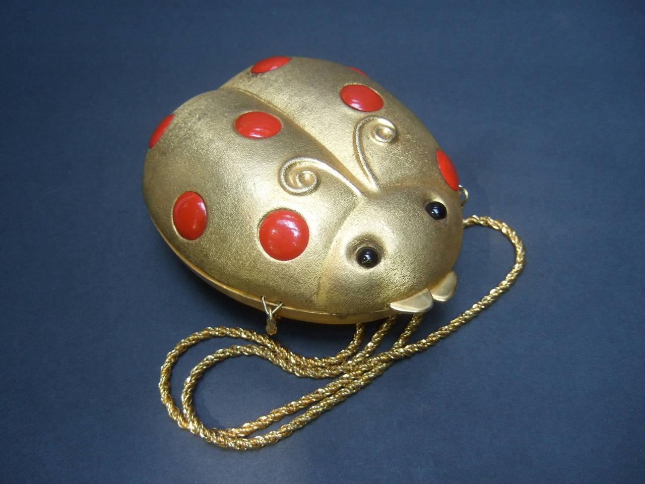 Saks Fifth Avenue Gilt metal lady bug evening bag Made in Italy c 1970 The charming gold metal minaudiare is embellished with  red enamel disc with black resin beaded eyes  The versatile design transitions from a chic clutch bag by placing the