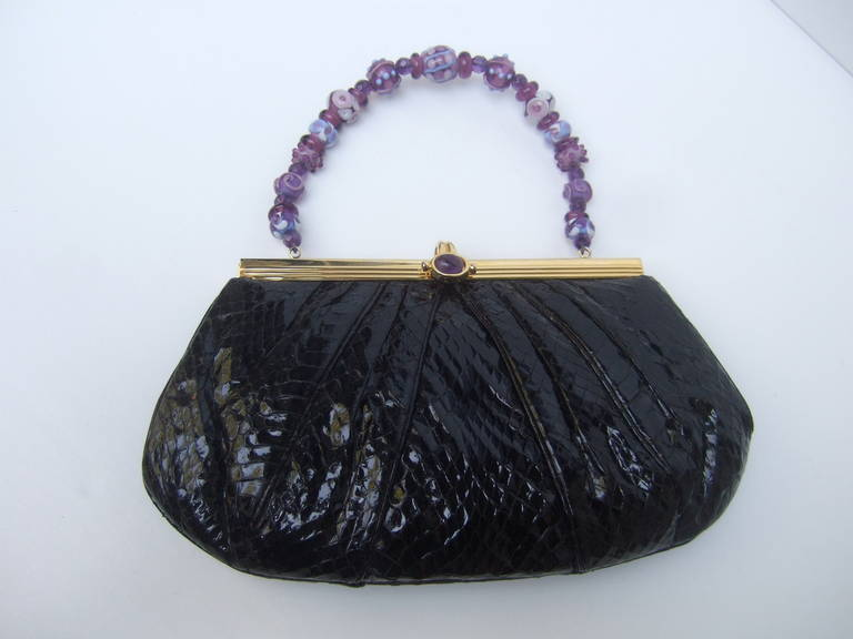 JUDITH LEIBER Black snakeskin evening bag with glass beaded handle   The posh designer handbag is embellished with a glass beaded handle with lavender & amethyst color beads & crystals   The gilt metal clasp is adorned with an amethyst color