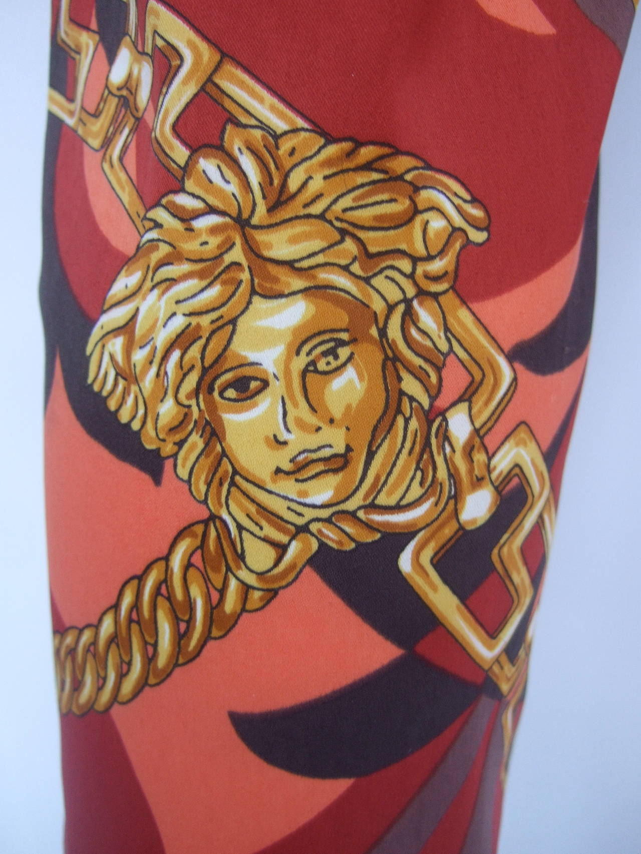 Versace Iconic medusa graphic print stretch jeans couture Size 28 The bold print is collage of Versace's signature Medusa's with lions & gold chains throughout. The background is a field of burnt orange, tangerine with reddish brown colors. The