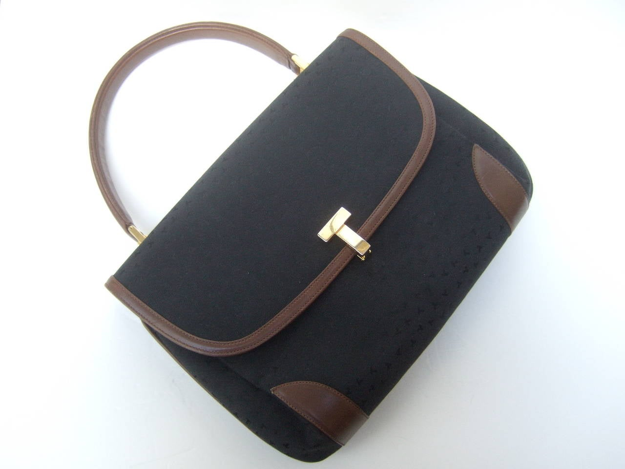 Tiffany & Company Black canvas leather trim handbag Made in Italy c 1980s The stylish handbag is covered with black canvas with Tiffany's subtle initials repeated throughout the fabric covering   The handle & sides of the Italian handbag are