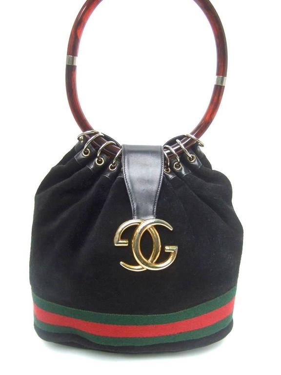 Luxurious rare black suede Gucci bag with lucite handle. 1970's. This ultra rare Gucci handbag is made of plush black suede accented with their signature red and green canvas stripe encircling it's lower section.  The clasp is adorned with Gucci's