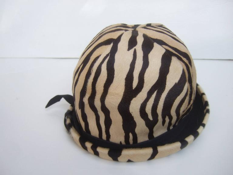 Saks Fifth Avenue Exotic zebra pony hair hat c 1970 The stylish retro hat is covered with stamped pony hair. The brim is accented with a subtle black ribbon  The interior is lined in fuchsia taffeta labeled  Saks Fifth Avenue   The mod retro