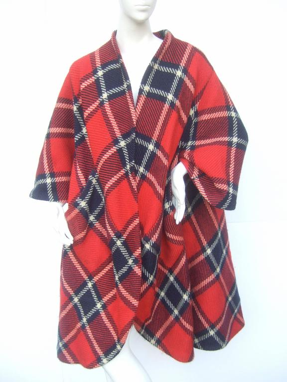 1960s Pauline Trigere Mod plaid wool swing coat  The stylish retro light weight coat is designed with bold tartan plaid wool fabric   The coat is designed with bracelet length sleeves and two wide slant patch pockets  on the front. The loose