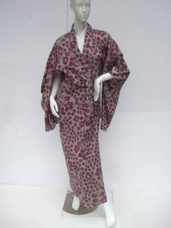 Japanese style flower print kimono robe c 1970s The exotic kimono is designed with a series of purple flower blooms and fallen flower pedals scattered throughout the print  Designed with traditional long exaggerated sleeves. The sheer light