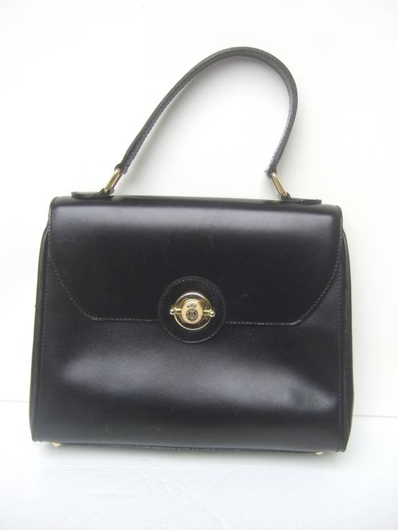 Saks Fifth Avenue Ebony leather handbag The chic Italian handbag is designed with supple black leather on the exterior  Adorned with a sleek gilt metal clasp mechanism with a small crown symbol The clasp is inscribed Honi - Soit -Oui  Mal .Y.