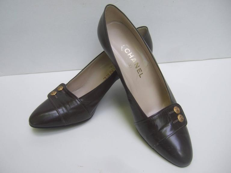 Chanel Classic gray / brown leather pumps The stylish leather pumps are designed with  muted gray / brown leather color covering   Each shoe is adorned with a pair of small gilt metal decorative buttons with Chanel's  iconic C.C. interlocked
