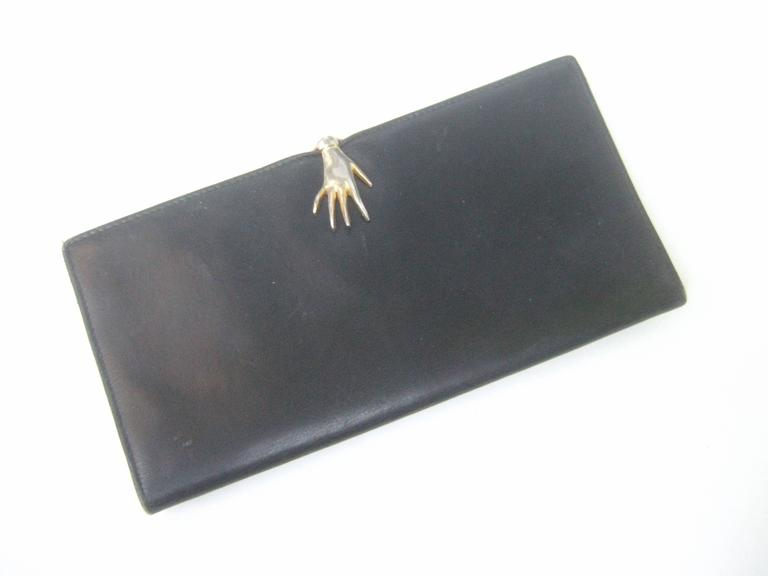 b073f568f4a2d5 Gucci Rare black leather hand clasp wallet c 1970s The stylish wallet is  adorned with a