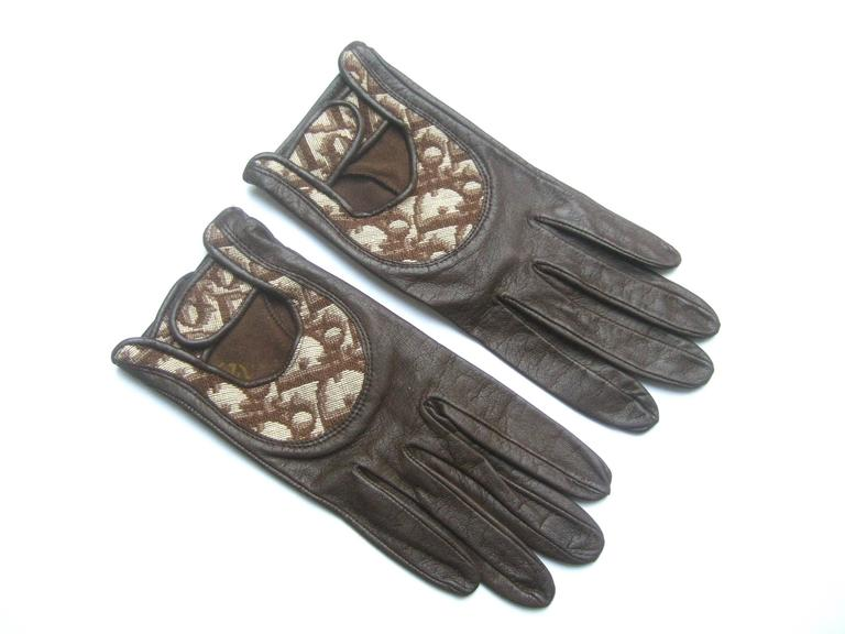 Christian Dior Chocolate brown leather driving gloves c 1970s The stylish designer gloves are constructed with supple dark brown leather  The top of each glove has a cloth panel insert with Dior's name repeated throughout; with a key