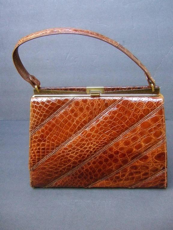 Chic genuine brown alligator handbag ca 1960s The stylish retro handbag is covered with exotic alligator skin that extends to the handle & clasp   Accented with sleek gilt metal hardware The interior is lined in ivory color vinyl  designed with a