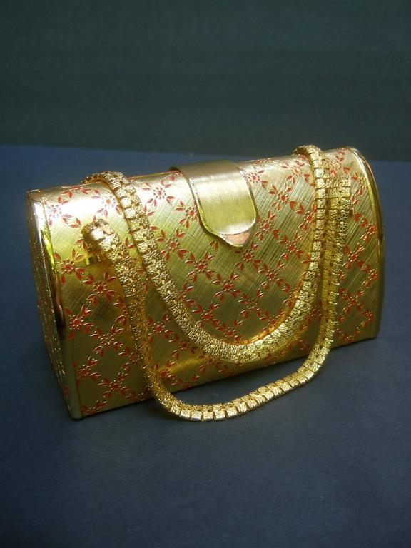 Saks Fifth Avenue Italian opulent gilt metal evening bag ca 1970 The elegant minaudi'ere is designed with luminous gilt metal Embellished with a red enamel jacquard design that extends to all sides  The posh evening bag is carried with a pair of