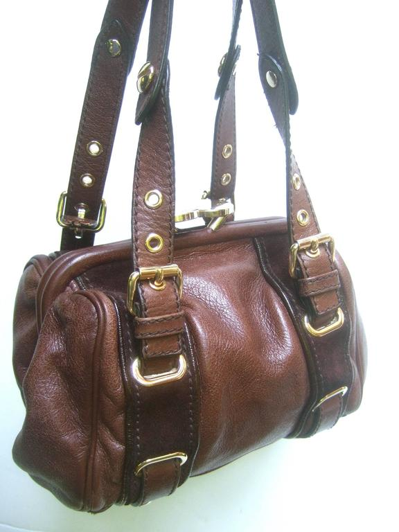 Marc Jacobs Italian brown leather diminutive handbag  The stylish compact Italian handbag is covered with supple mocha brown leather   Designed with sleek gilt metal hardware and buckles  Accented with a pair of brown suede vertical stripes The kiss