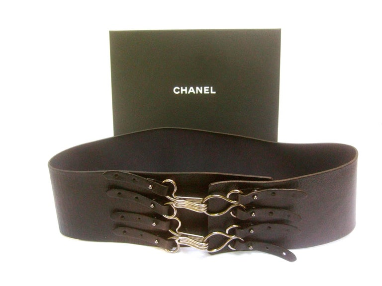 Chanel bold wide black leather belt in Chanel box  The stylish high fashion belt is designed with a pair of large silver metal clamps. Each clamp is inscribed  Chanel   The unique design allows the silver metal magnetic  clamps to adjust over three