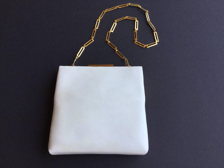 Fantastic early Pierre Cardin white patent leather bag with alternating rectangles of textured and glossy, silver and gold, metal pieces. Each metal rectangle is carefully riveted to the front with tiny delicate studs. So on trend! Think Paco