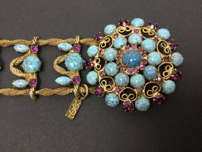 Magnificent 1970's Yves St. Laurent gilt metal belt of burnished twisted mesh ropes. Absolutely encrusted with art glass faux turquoise cabochons and faceted faux amethyst crystals. Large central buckle with a hidden clasp behind. Excellent