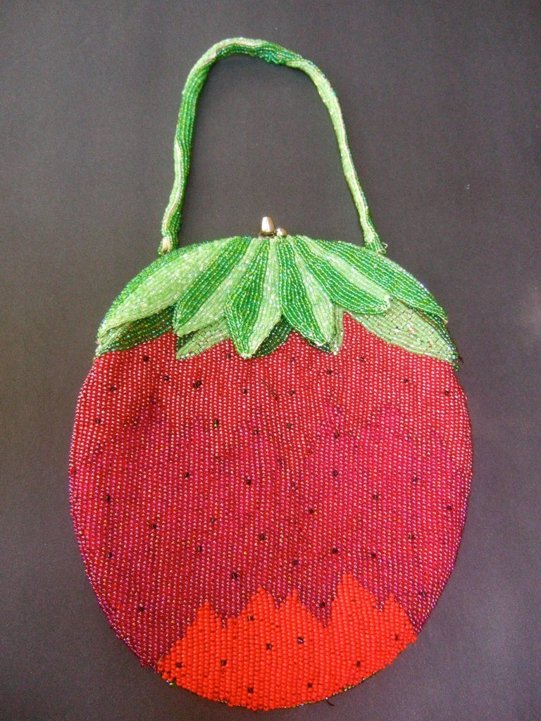 Whimsical glass beaded strawberry evening bag c 1970s The unique glass beaded purse is designed with rows of intricate glass beading throughout  Suspended from a matching green glass beaded handle  The interior is lined in red satin designed with a