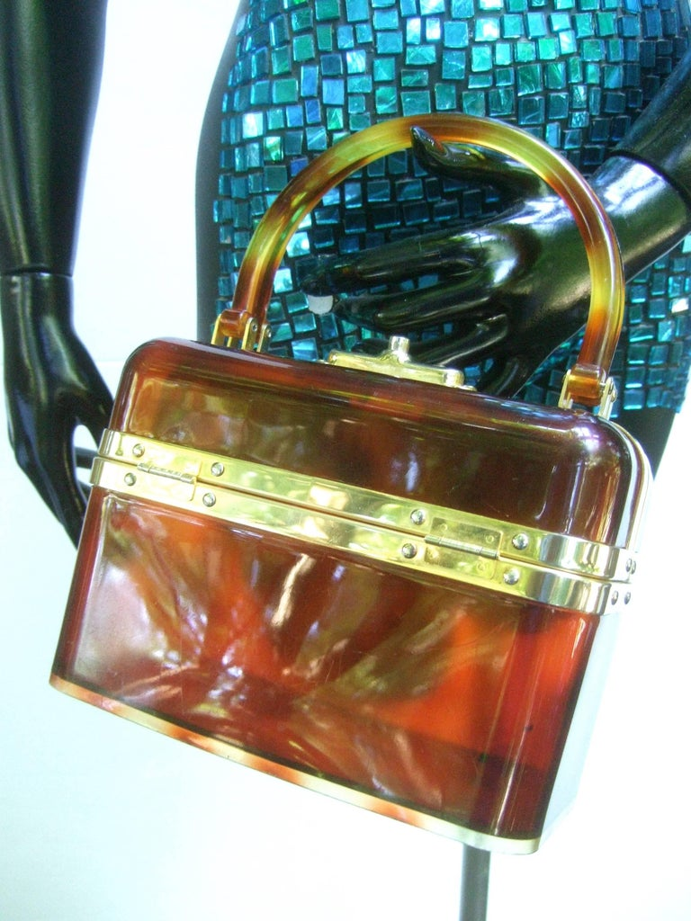 1970s Sleek French tortoise shell lucite box purse  The mod retro handbag is constructed with brown honey color translucent lucite panels   Framed with polished gilt metal hardware designed with a pair of lucite swivel handles  The top opening is