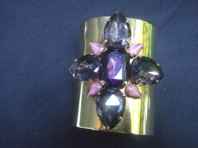 Erickson Beamon Wide gilt metal pastel crystal jeweled cuff bracelet  The shiny gilt metal cuff is embellished with a pastel amethyst color glass crystal at the center, surrounded with pale muted lavender  color glass settings & small pale pink