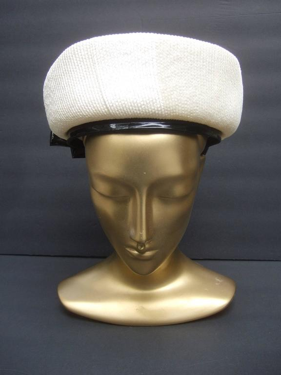 Lilly Dache Parisian style bow trim hat c 1970 The stylish retro had is designed with off white raffia accented with a large black patent leather bow on the back side  The interior brim of the hat is framed with a patent leather band that