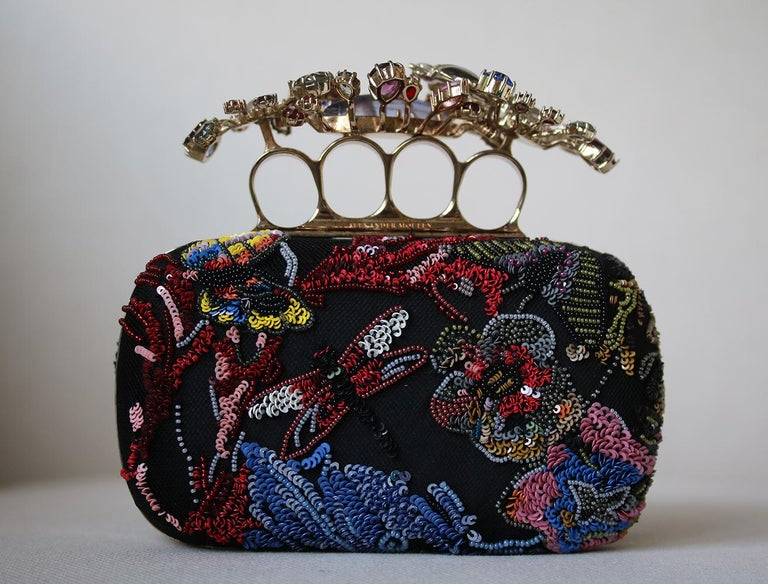 Multicolour beaded wonderland embroidery Short Knuckle Clutch; features Swarovski crystal floral knuckle holder, suede body of the clutch and a chain strap. Brass hardware with a gold finish. 80% Brass, 20% satin.  Dimensions: W 16 x H 12 x D 5