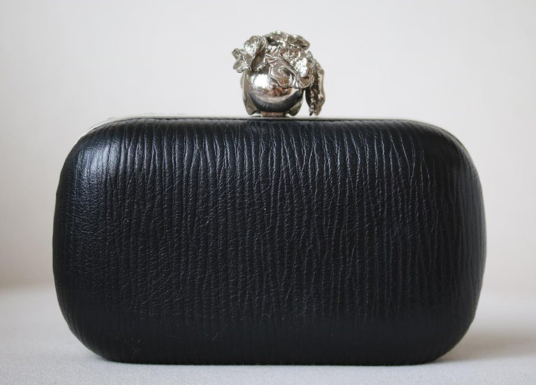 Make a statement with this bold Alexander McQueen Black Textured Leather Poppy Skull Box Clutch Bag. Featuring box frame silhouette, this clutch is covered in gorgeous black grained leather. The clutch closes with a silvertone metal and Poppy