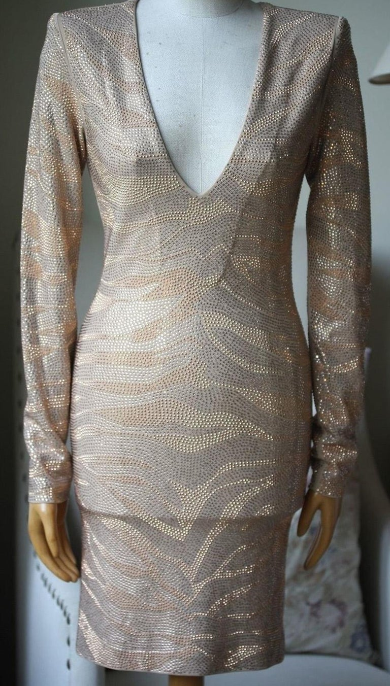 Balmain's long-sleeved beige mini dress is a major party piece. Covered in shimmering sequins to resemble a tiger motif, this silk-lined crepe piece has a close fit, a flattering V-neck and padded shoulders - a brand signature.   Size: FR 36 (UK 8,