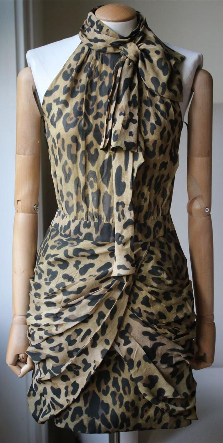 Brown tonal silk leopard dress from Balmain featuring a band collar with a pussy bow detail to the front, a sleeveless design, draped details, a rear zip fastening, a fitted waist and a short length. 100% Silk.  Size: FR 36 (UK 8, US 4, IT