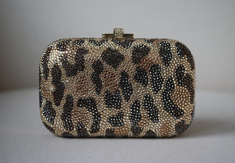 Leopard-print hard box clutch with hand-placed fine crystal embellishment. Judith Leiber clutch has a gold frame and removable chain-link handle that can be hidden inside the bag, a push-clasp at top and is fully lined in gold leather.  Dimensions: