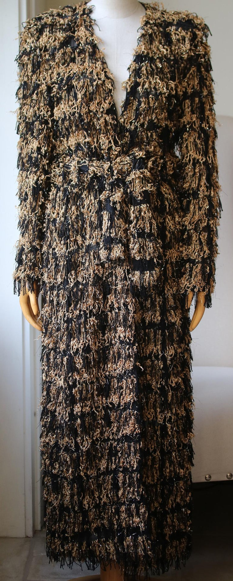 Exuding the extroverted aesthetic of Balmain, this longline cardigan is rendered in a metallic fringed tweed, lending a dose of the brand's signature glamour to your portfolio. Finished with exaggerated shoulders and a tie belt to define the waist,