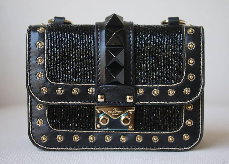 Valentino Mini Rockstud Bead Embellished Shoulder Bag. Black Leather Embellished With Beaded Body. Signature Pyramid Studs. Bordered With Gold Tone Studs. Gold Tone Hardware. Pushlock And Flap Closure. Back Slip Pocket. Suede Lined Interior.