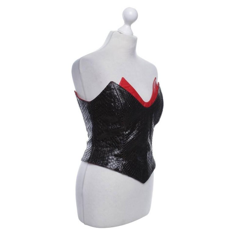 RARE and Collectible Thierry Mugler Couture  Black and red silk and python skin corset from Thierry Mugler Vintage featuring a strapless design, a sweetheart neckline, a fitted silhouette, a boned waist, a red silk trim and an all-over python skin