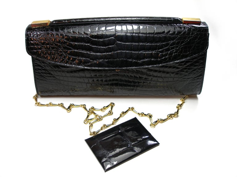 Nice and Perfect compagnon ! Delvaux Clutch or Evening Bag And small Pocket Miroir dimensions :  7 x 10 cm or 2.75 x 3.9 inches Crocodile Leather  Amovible chaine strap  Dimensions :  31 x 14 x 4 cm or 12.2 x 5.5 x 1.57 inches Strap : 103 cm or