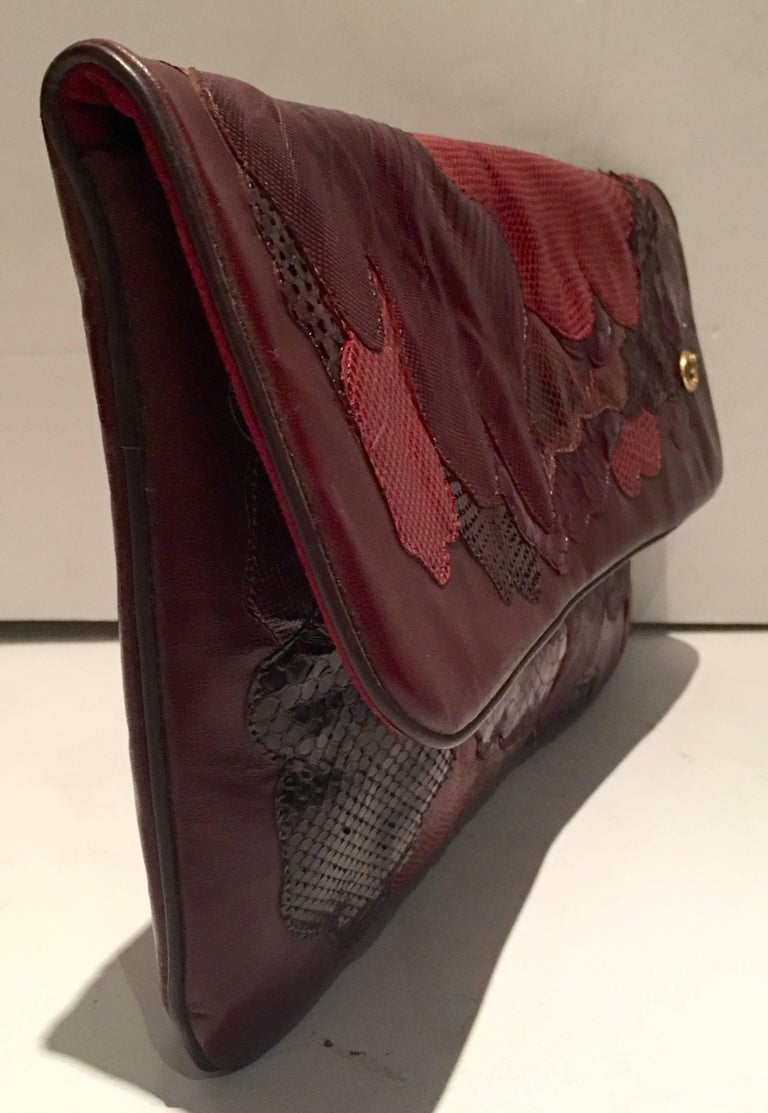 Vintage Italian Leather & Python Patchwork Clutch Hand Bag, By Carlos Fiori. This pristine oxblood leather hand bag features several exotic species in tones of deep and vibrant reds with brown hand stitched in a abstract patchwork pattern, both