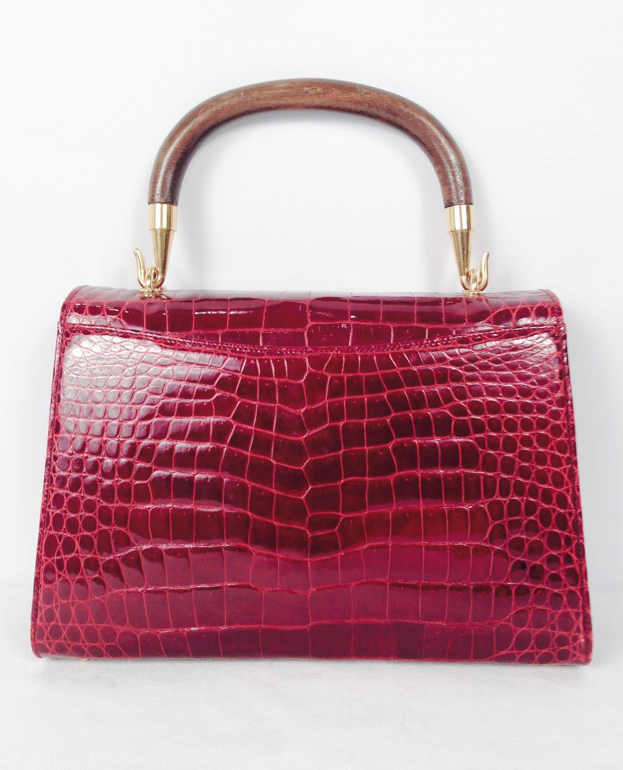 Vintage Gucci Burgundy Crocodile Handbag is an ode to the exalted craftsmanship that defines the house of Gucci.  This handbag perfectly blends form, function, and fashion!  Soft, supple burgundy crocodile is paired with wood and gold tone hardware.