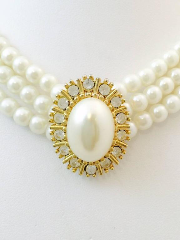 """Ahhh, Chanel!  Coco made pearls a wardrobe staple!  This amazing 16"""" choker is designed with three strands of 5.5-6.0MM faux pearls culminating in an attached center station in gold tone featuring an oval faux pearl measuring 18x13MM faux pearl."""