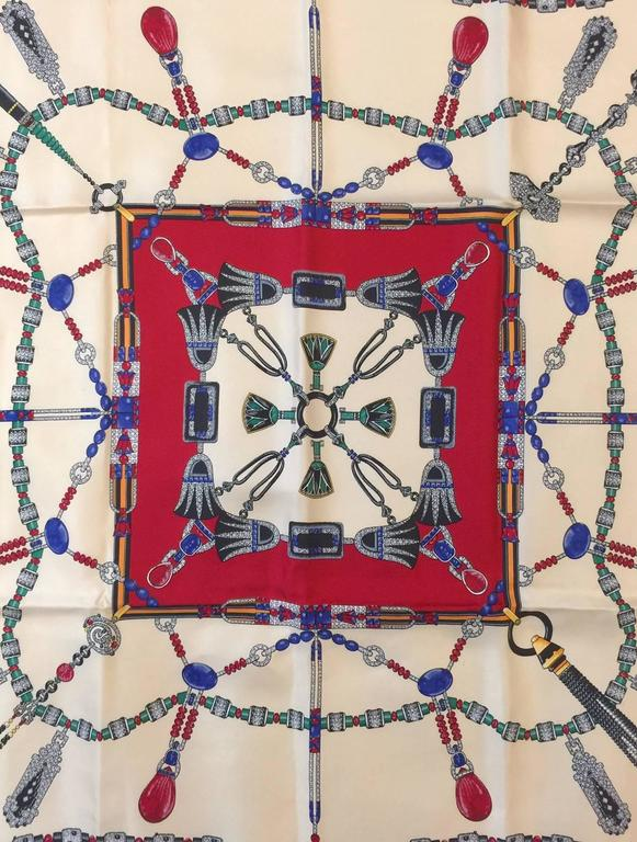 This silk twill scarf proves that Cartier is not just a purveyor of some of the world's greatest gems!  Fashion is also a strong suit!  Scarf features exquisite silk fabric, and primarily ivory and signature red colorway.  Printed with depictions of