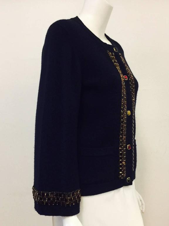 """Quintessentially """"Coco"""" navy cardigan is crafted from the finest cashmere in the United Kingdom!  Features round neckline, monk bracelet sleeves, two pockets and 5 cabochon gripoix buttons in varying jewel tone shades with just the right amount of"""