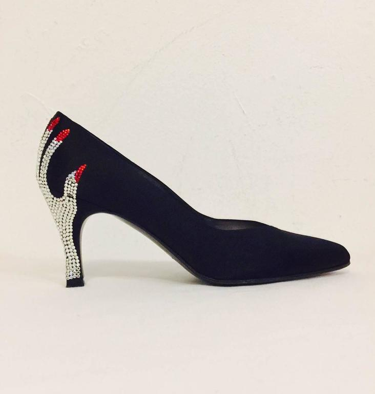 Make an entrance and an unforgettable exit when wearing these whimsical black satin pumps from Stuart Weitzman.  Each