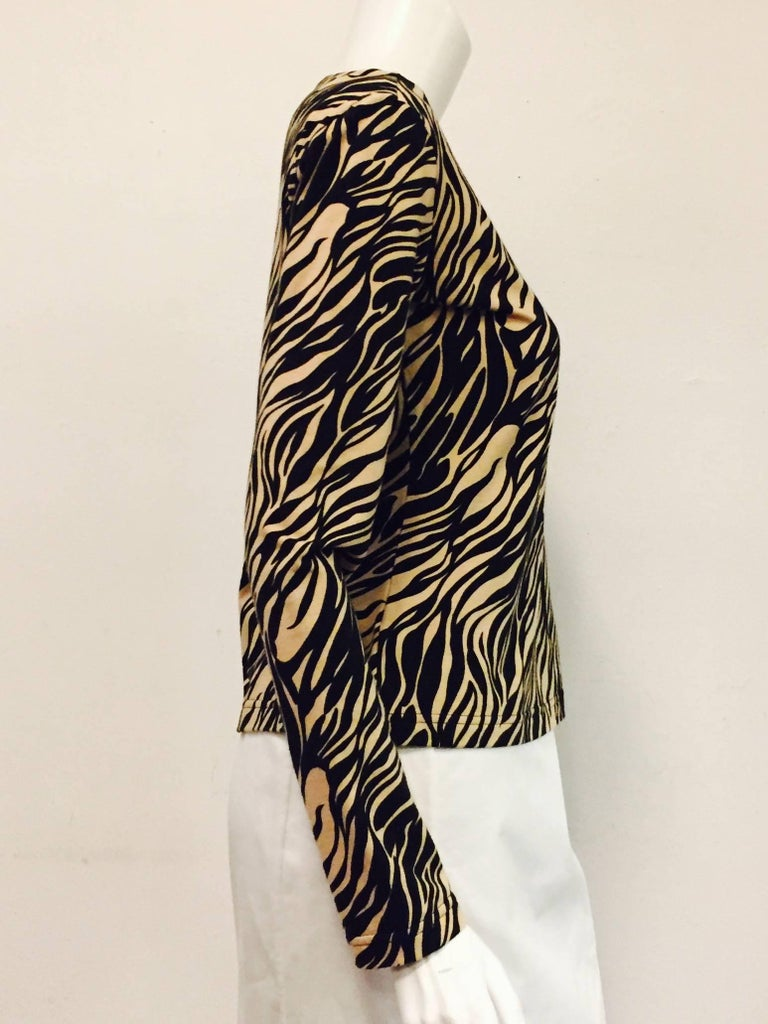 Featuring boat neckline and long sleeves, this Versace tiger print top is worthy of any vamp.  Ultra-luxurious soft cotton knit is versatile enough to be worn with a casual pair of slacks or beneath a smart jacket.  Excellent Condition!  Made in